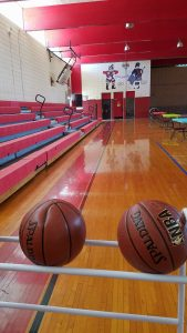 view of gym with baske tballs in foreground