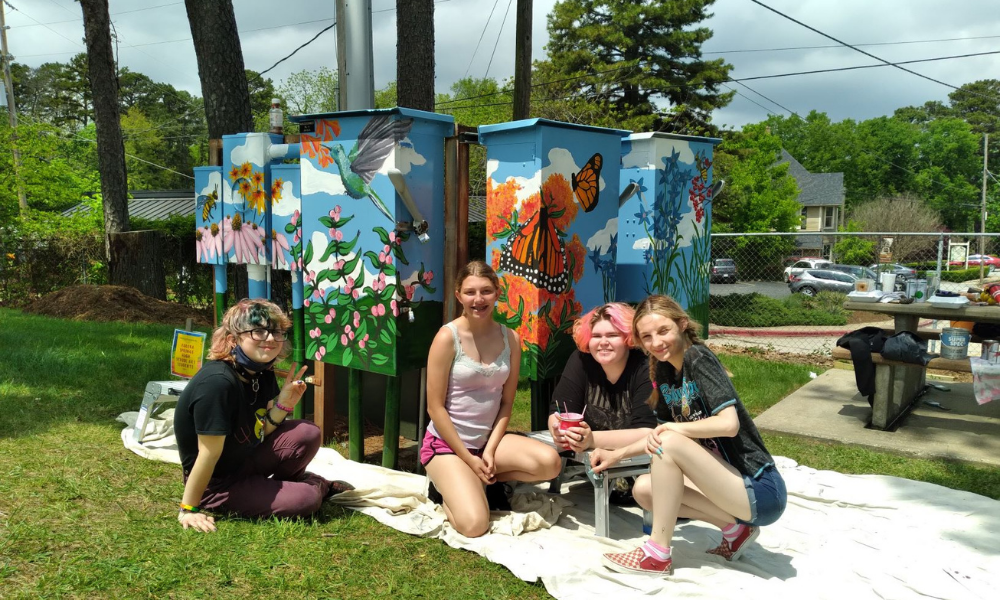 Students painting utilities boxes with flowers and butterflies