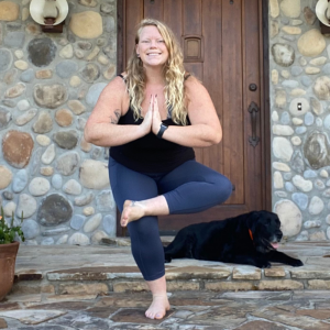 Young woman standing in front of stone building in a yoga pose