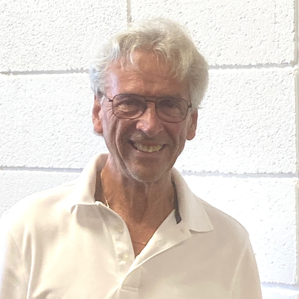 older man with grey hair smiling in front of a white wall